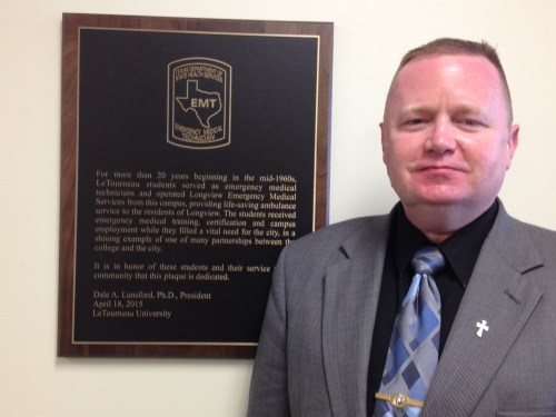 my husband Ray, by the plaque dedicated for LeTourneau University's original EMS program