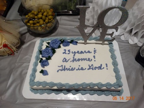 "The party cake with a silver border & purple flowers. It reads, ""25 years & a home. This is God!"""