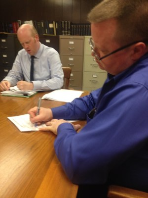 Ray signing papers at the house closing