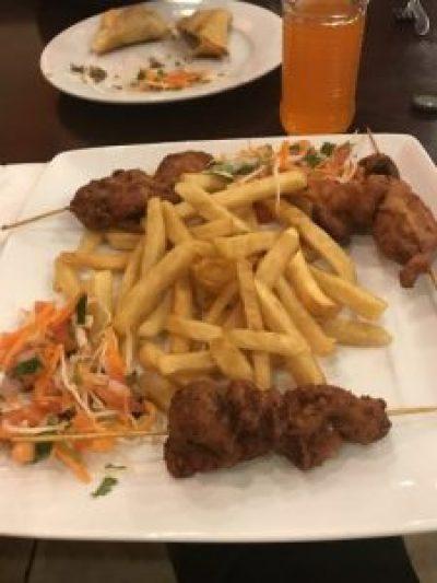 Mshikaki (Chicken skewers), fries, and Kachumbari (salad)