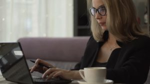 woman writing on laptop with coffee