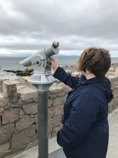 Leah putting Euro coins in telescope
