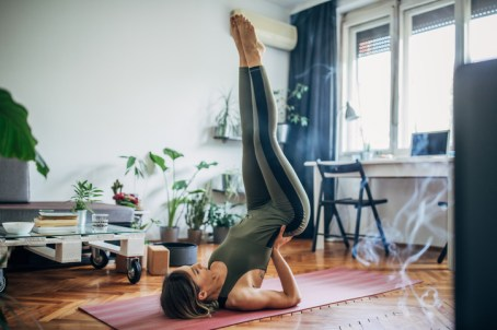 Woman lying on upper back and holding her lower back in balance. Image Source: Istock