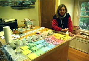Beth, painting the etching proof strips rainbow colors with translucent acrylic paint.