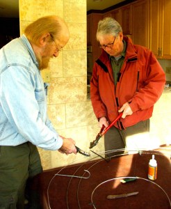 Armature. Bob Neville and Tom Chippendale assist in snipping metal hooks.