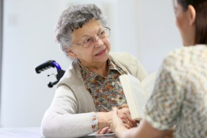 Homec arer reading book to old woman in nursing home