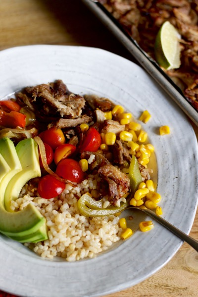 Burrito bowls made with carnitas are great for a crowd, especially with rice, fajita veggies, beans, crispy corn, and avocado.