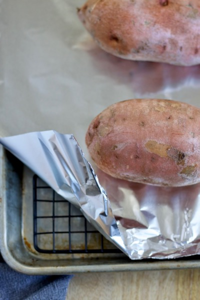 the baking pan set up for baked sweet potatoes is a rimmed baking sheet, a cooling rack, and a piece of tin foil