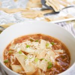 a loaded bowl of crockpot chicken tortilla soup with crunchy baked tortilla strips
