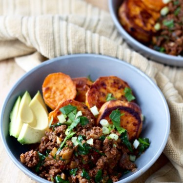 A veggie-packed taco bowl with roasted sweet potatoes and slices of avocado