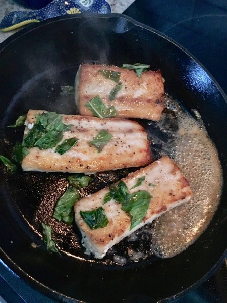 tilting the cast iron skillet and basting mahi-mahi fillets with melted butter