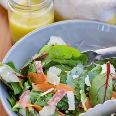 A big bowl of salad with a jar of golden lemon vinaigrette dressing