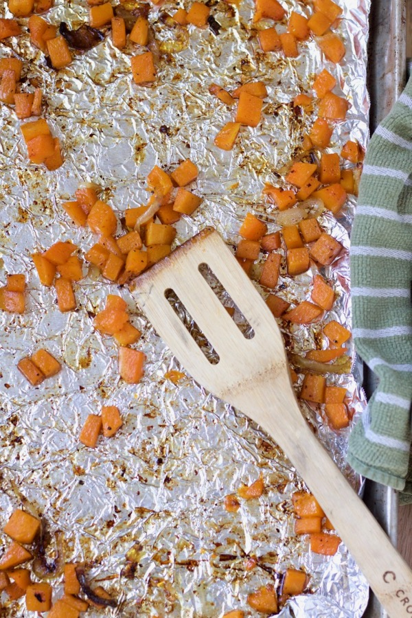 roasted butternut squash with onions cooked in bacon grease on a sheet pan