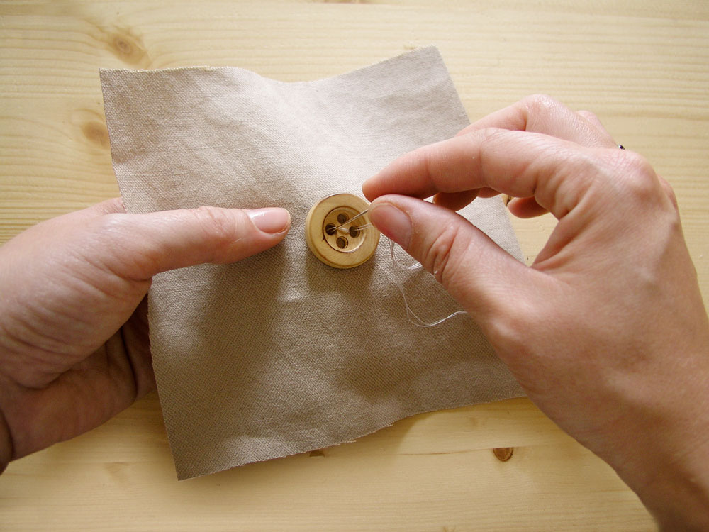 Sewing button by hand