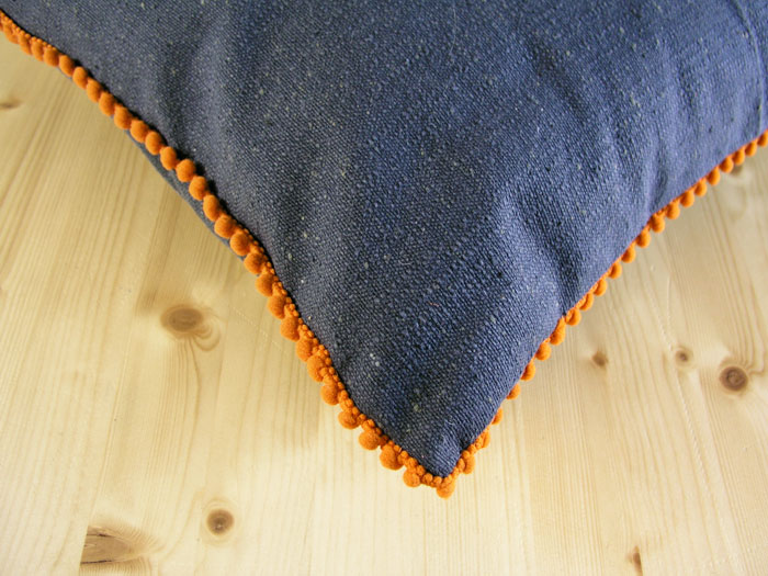 Hand-sewn decorative ribbon on the edges of the cushion