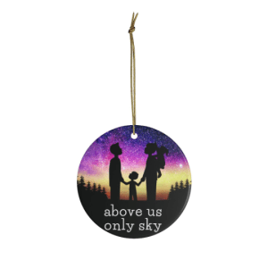 ceramic ornament shows family with two adults, not gender specific, and two children. one child has a ponytail and is riding piggyback. the other child is between the adults and holding their hands. The family is looking at the sky . the sky features an image of the northern lights