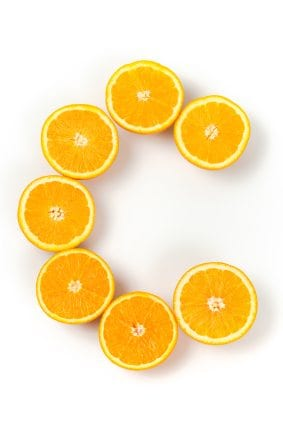 Several pieces of fresh oranges in the form of letter C. Isolated on white.