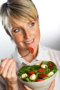 young blond woman eating fresh salad close up