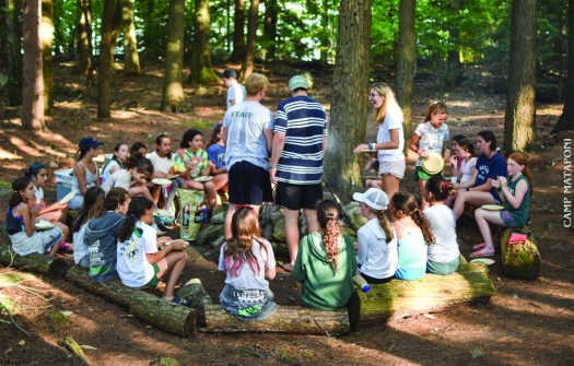 campers at camp mataponi huddle around the fire