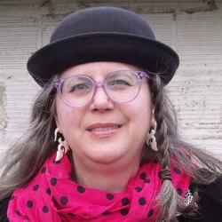 Photo of woman wearing black hat, pink scarf. Jackie jump starts Walch Communication