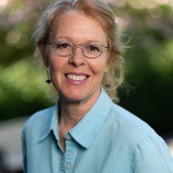 Woman smiling, wearing glasses, blue shirt. Artist Susan Curington