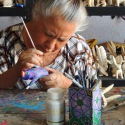 older woman painting artisan