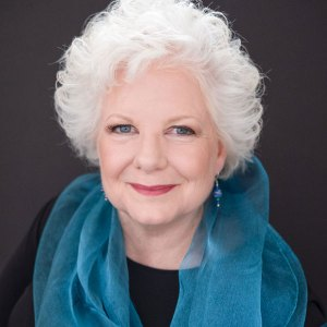 Photo of woman with white hair, wearing a blue scarf.