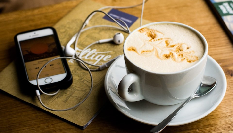 Coffee cup and smartphone playing a podcast