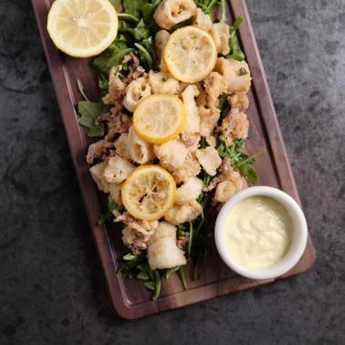 calamari on board with lemon wedge and aioli sauce