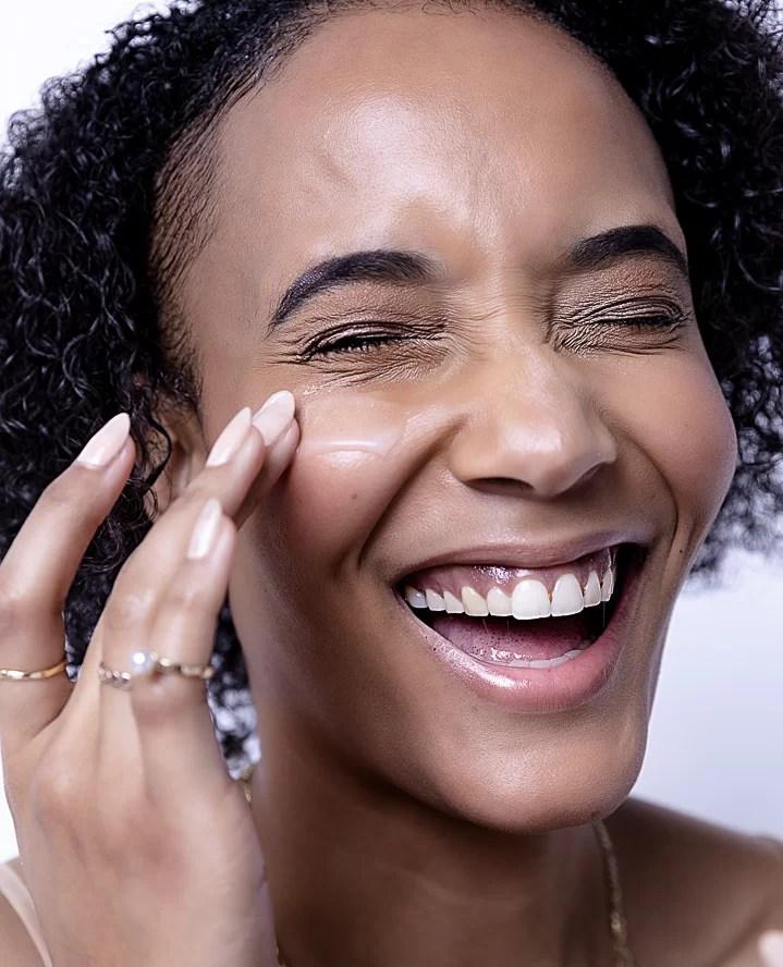 Femme souriante appliquant de la crème sur son visage