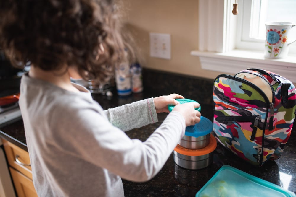 girl packing lunch in reusable containers