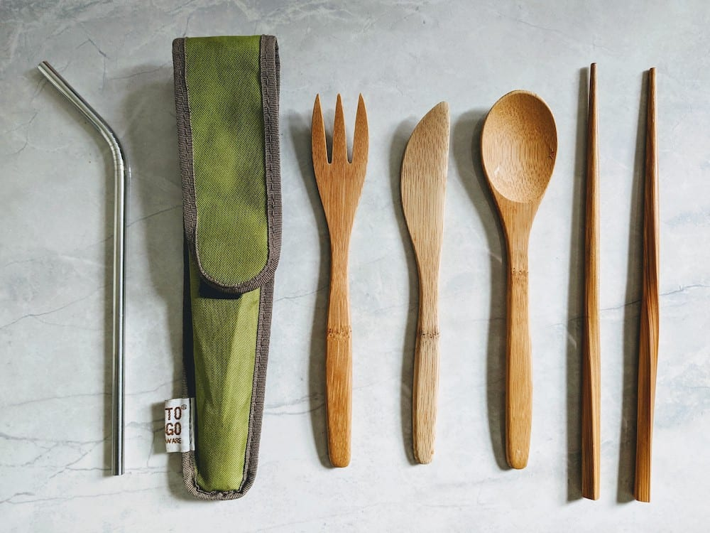 metal straw and bambo fork, knife, spoon and chopsticks on a marble counter