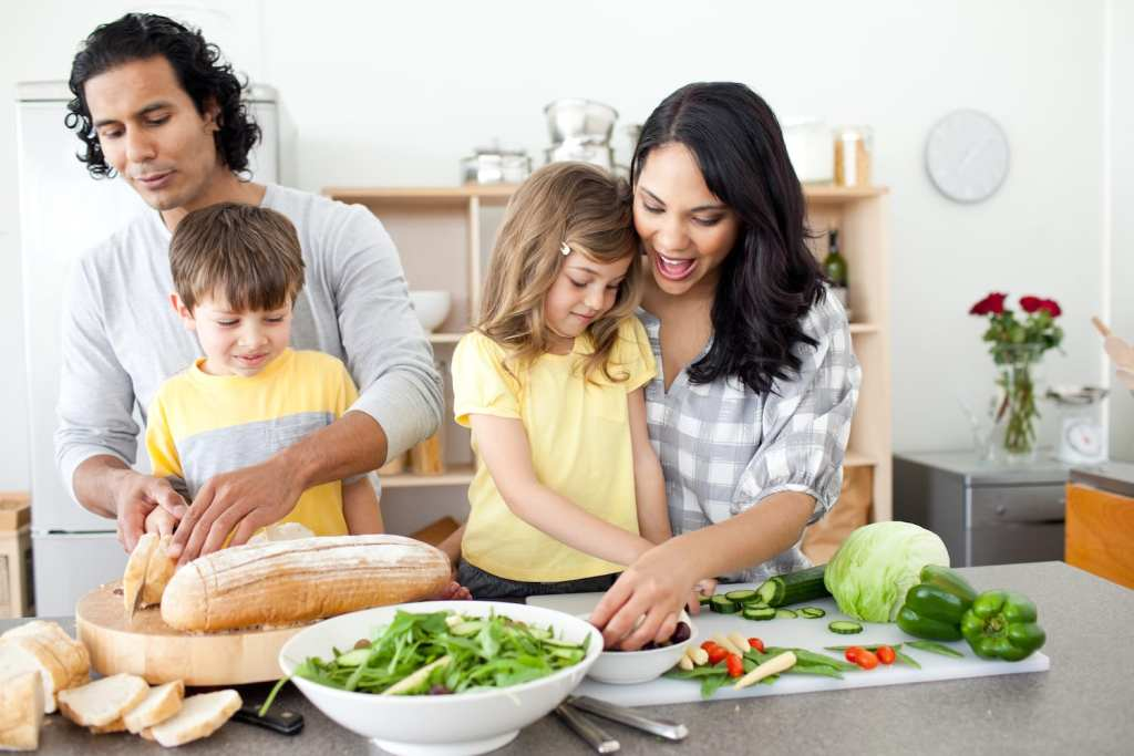 Mom, dad, son, and daughter preparing a healthy meal