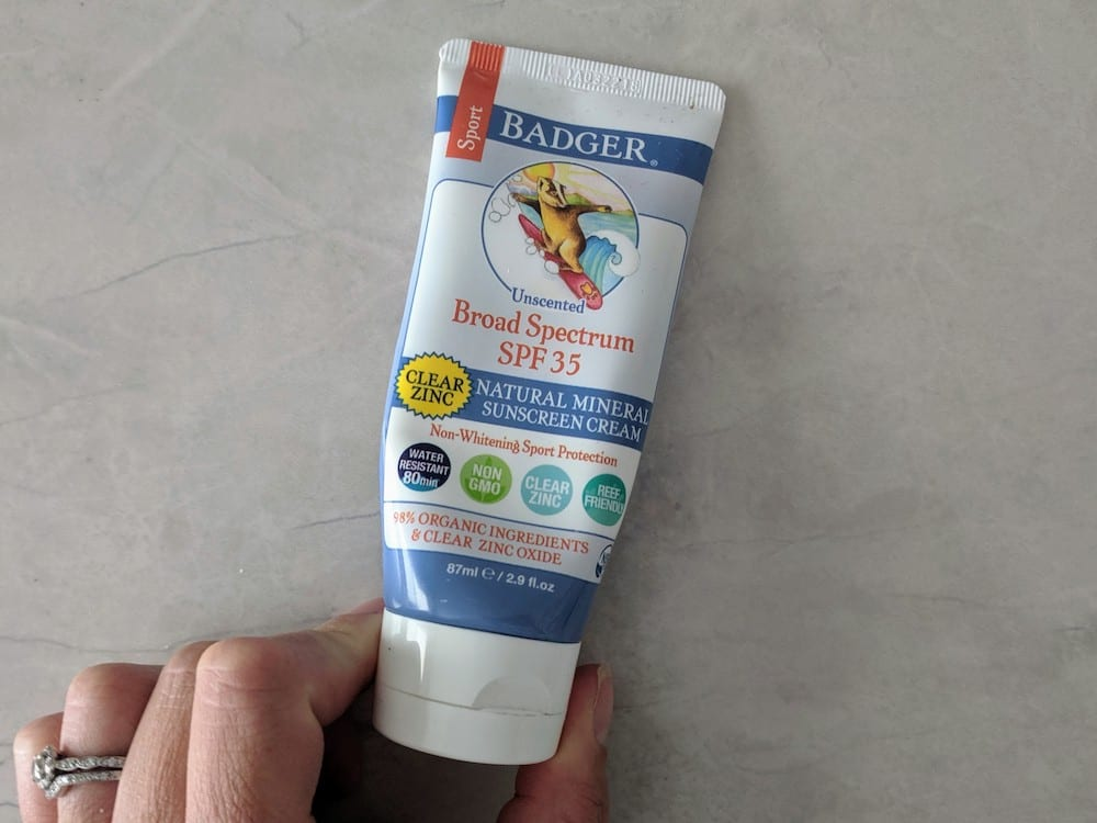 Hand holding Badger sunscreen