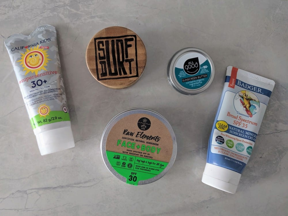 California Kids, Surf Durt, All Good, Badger, and Raw Element Sunscreens on a marble counter