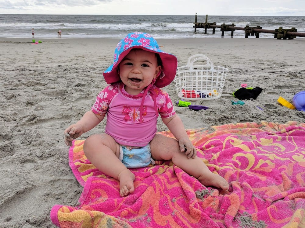 baby at the beach looking happy