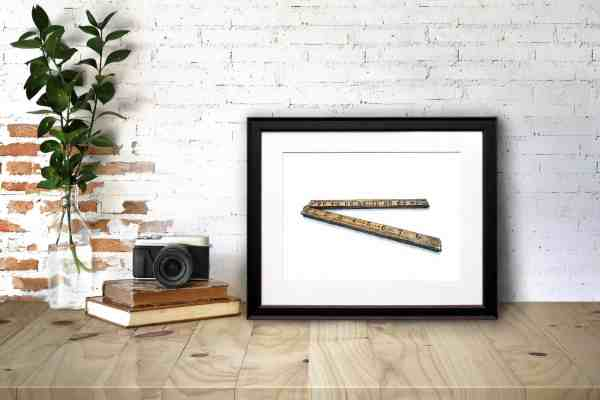 Print of an antique folding wooden ruler in a black frame sitting on a wooden desk leaning against a white brick wall