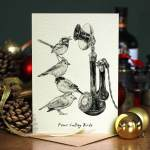 Christmas card of a black and white drawing of four birds standing on top of each other next to a vintage telephone on a table