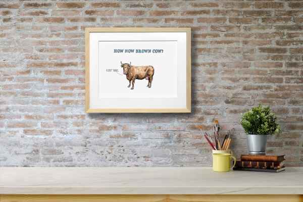 Print of a brown cow in a light wood frame on a red brick wall above a white shelf with a plant, books and pens