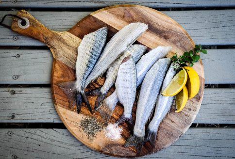 Fische auf einem Holzbrett mit Zitronen und Kräutern
