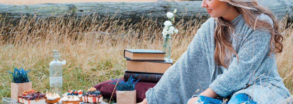 Frau sitzt bei Picknick auf Wiese