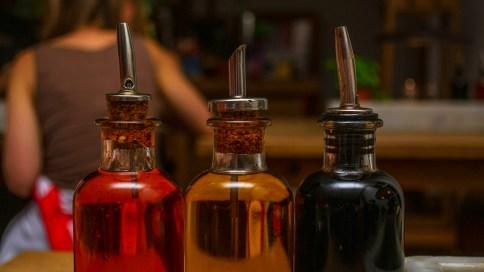 Drei Flaschen mit Essig und Öl