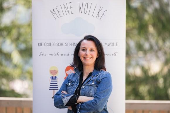 Sabine Fallmann-Hauser: Gründerin von Meine WOLLKE vor einem Meine WOLLKE Plakat