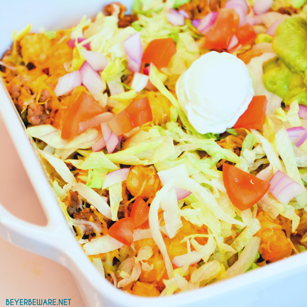 Totchos are the tater tot version of nachos with all your favorite taco toppings like ground beef, lettuce, tomatoes, and cheese.