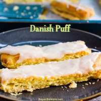 Almond Danish Puff Pastry has a flaky thin crust with a soft eggy bread layer that is drenched in almond flavoring and then covered with a light almond icing.