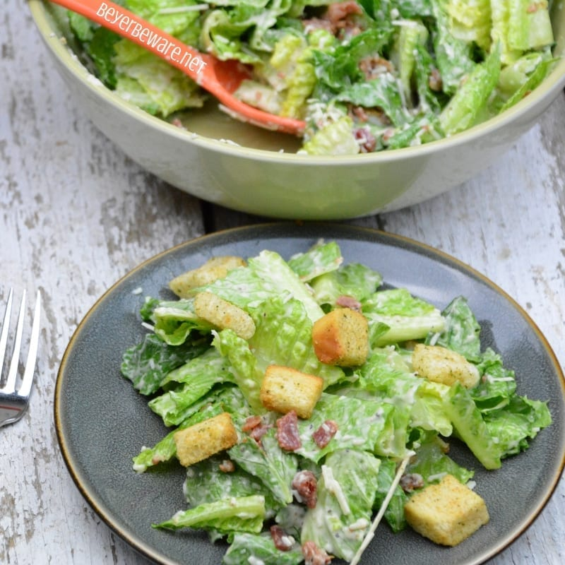 Easy bacon caesar salad is a simple combination of the basic Caesar salad ingredients of romaine lettuce, parmesan cheese, caesar dressing and croutons and taken up a notch with the addition of bacon.