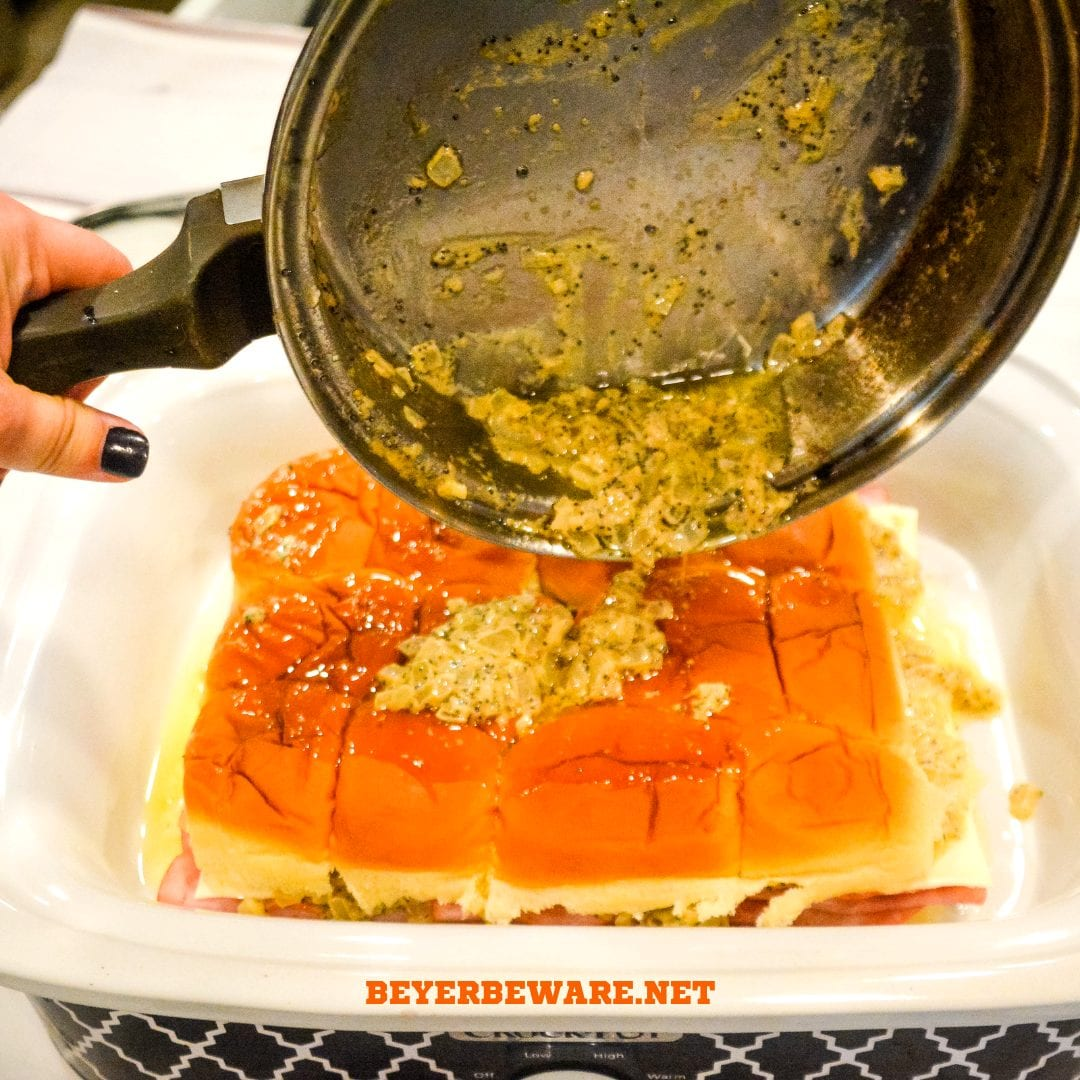 Crock pot Hawaiian roll ham sandwiches are the warm buttery mustard ham sandwich recipe made with onions, poppy seeds, and Swiss cheese without needing to bake them with the same results.