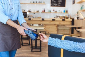 Server handing a point of sale terminal to a customer in a cafe. A nudge can increase tips!