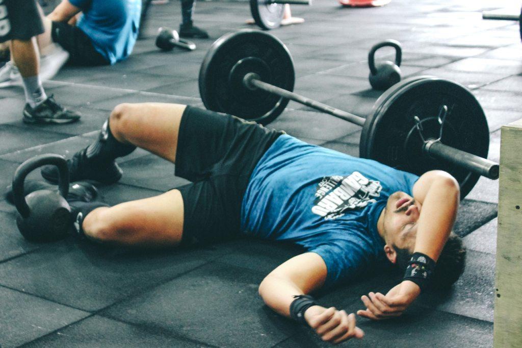man-tired-on-gym-floor