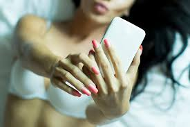 woman holding phone and lying on bed